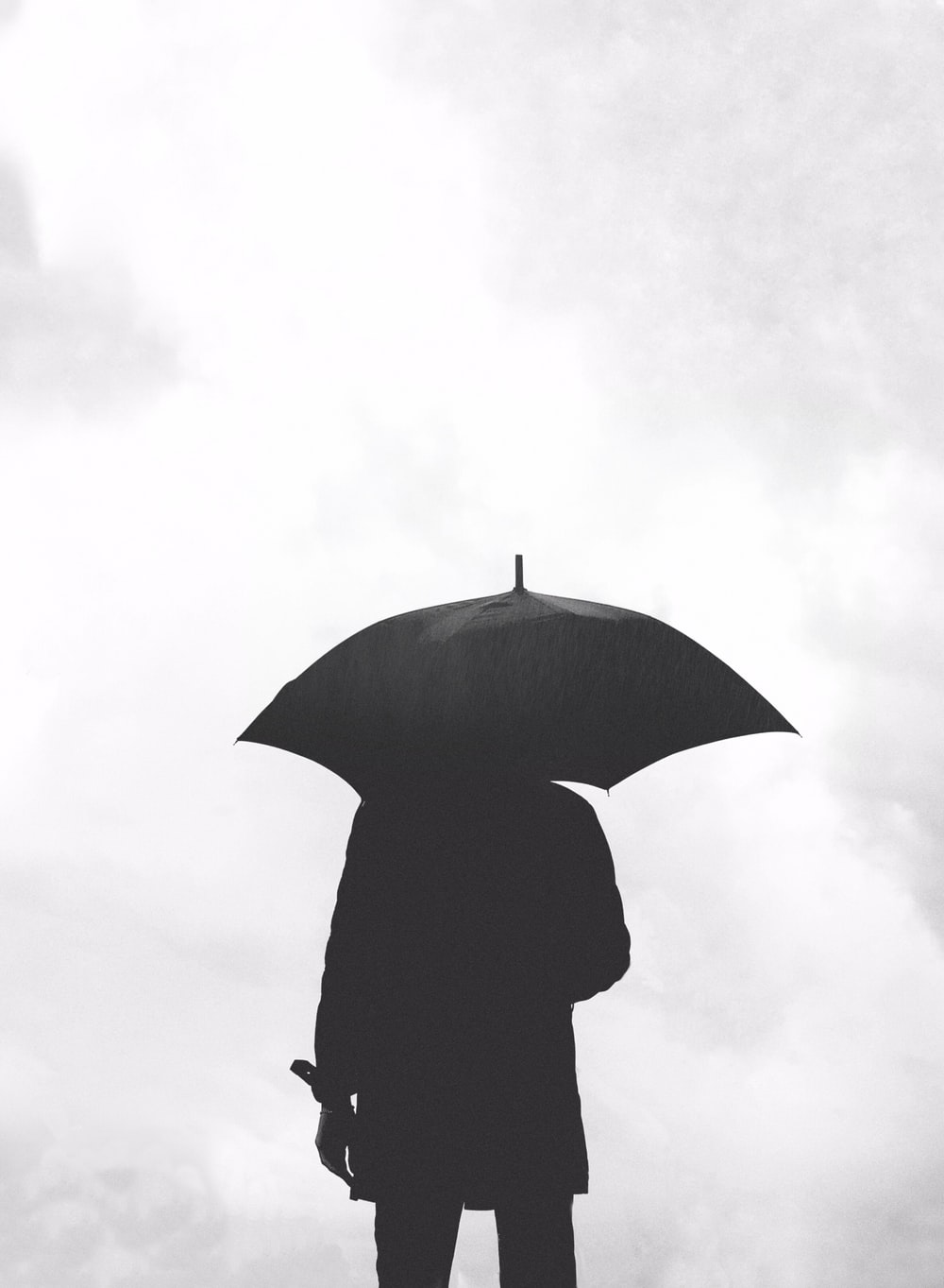silhouette of person under umbrella under cloudy sky