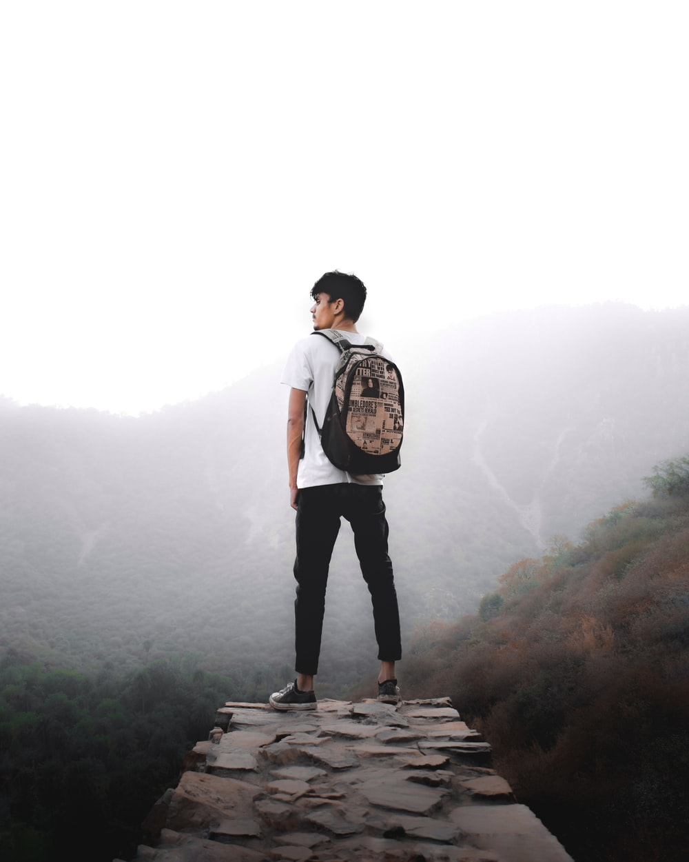 man in white t-shirt and black pants standing on rock formation during daytime
