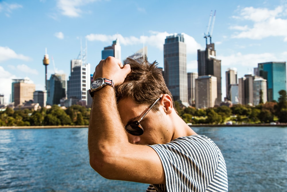 man in black and white striped shirt wearing black sunglasses looking at city buildings during daytime