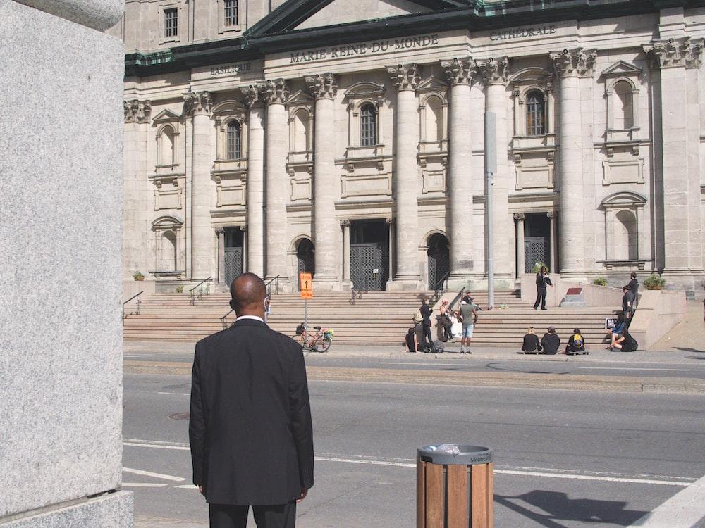 man in black coat standing on gray concrete floor during daytime
