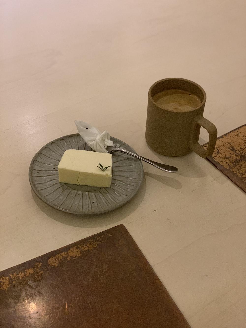 stainless steel fork beside white ceramic mug on brown wooden table