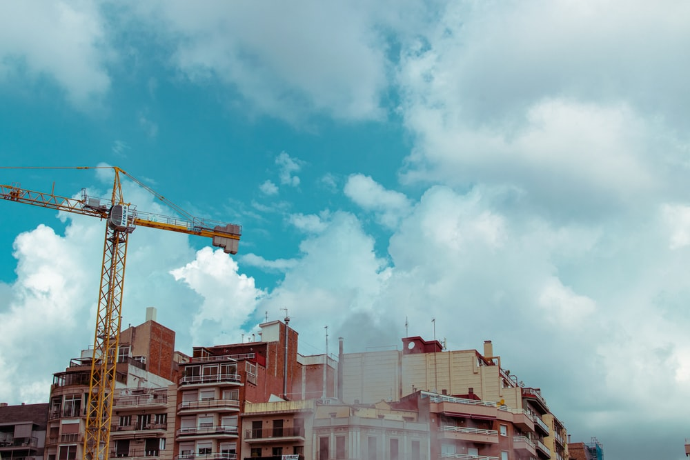 white and brown concrete buildings under white clouds and blue sky during daytime