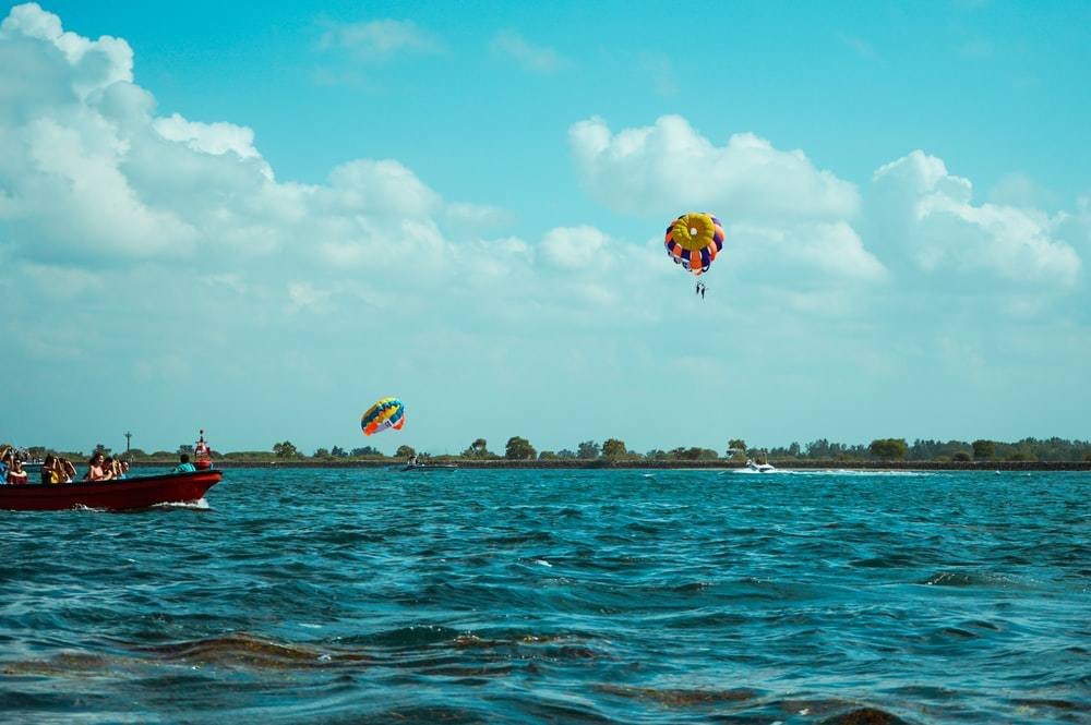 people riding red and yellow parachute over blue sea under blue sky during daytime