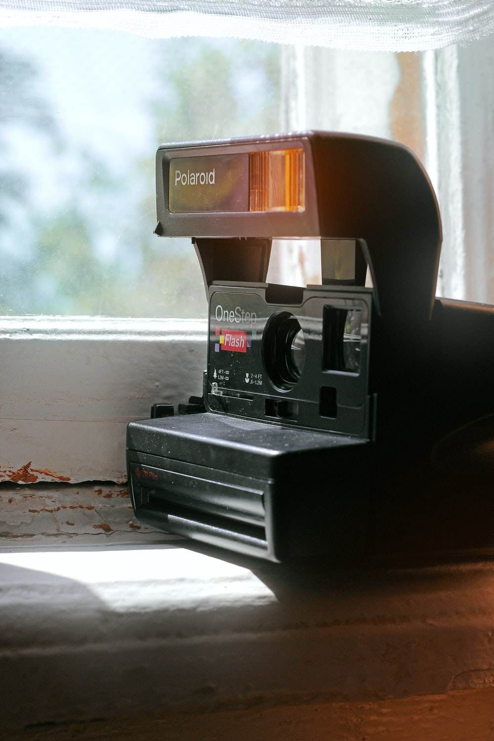 black and red polaroid camera on brown wooden table