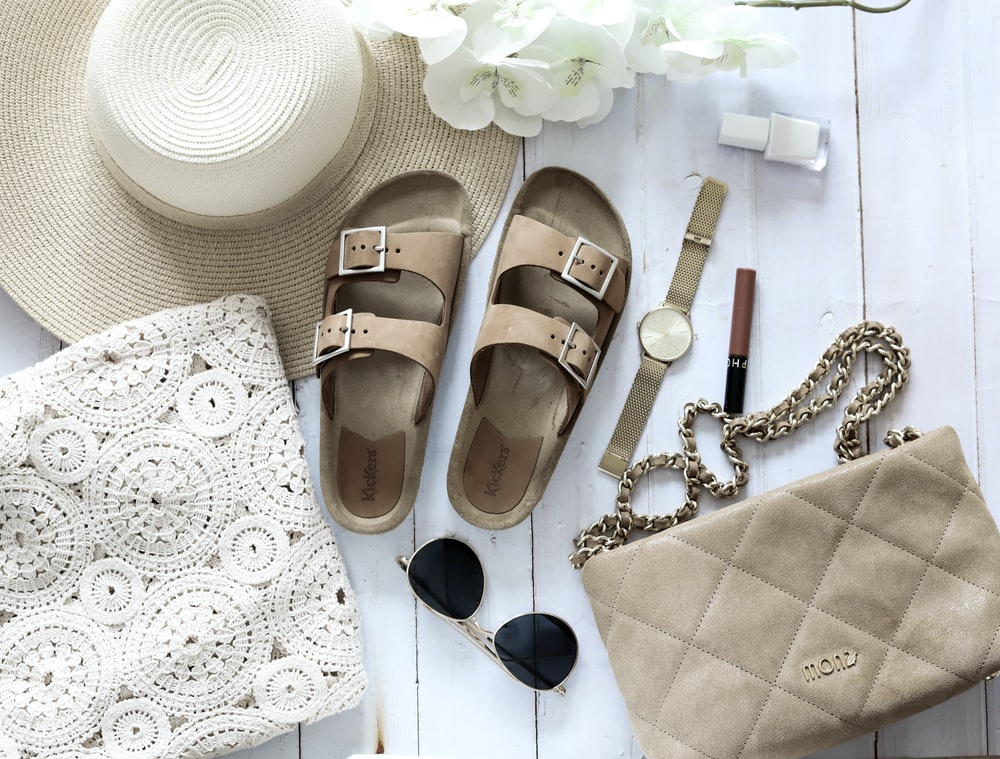brown leather sandals beside black sunglasses