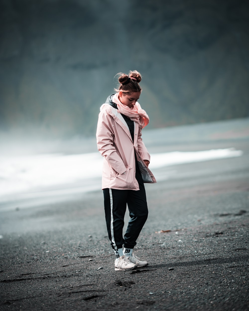 woman in pink coat standing on road during daytime