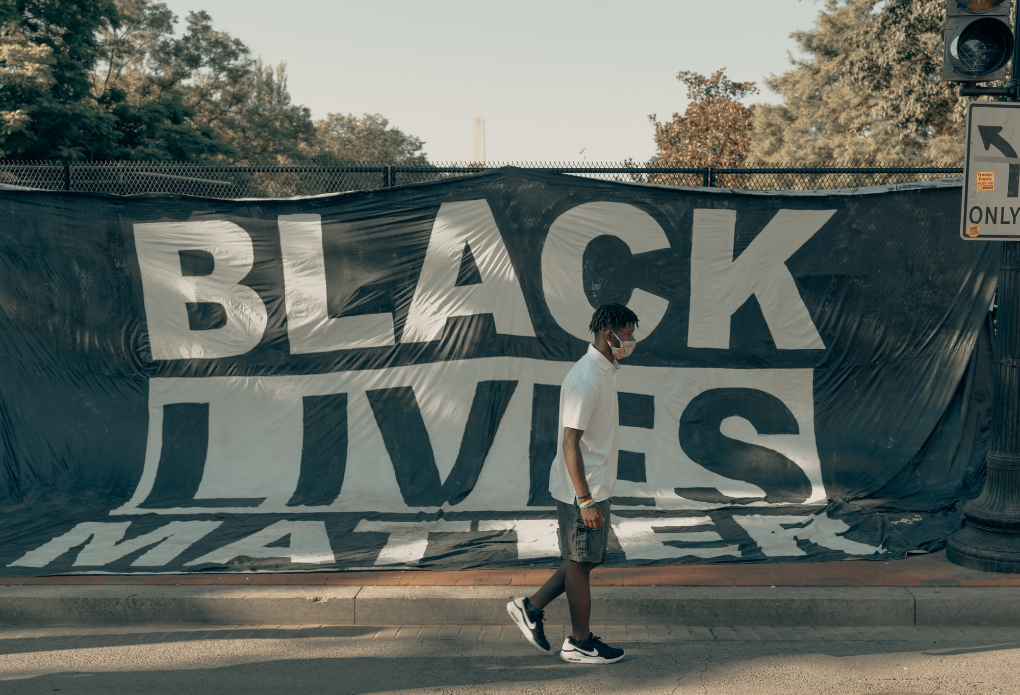 Man walks in front of a Black Lives Matter flag (IG: @clay.banks)