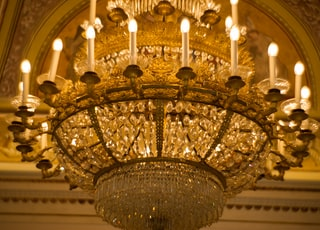 gold and white chandelier turned on in a building