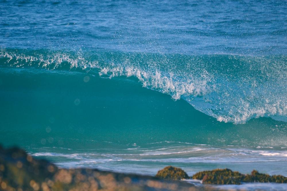 blue sea waves crashing on brown rocky shore during daytime