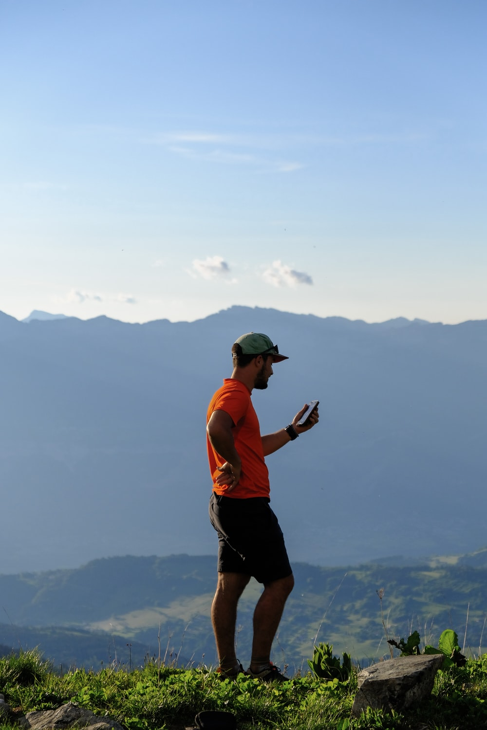 man in orange tank top and black shorts holding camera standing on top of mountain during