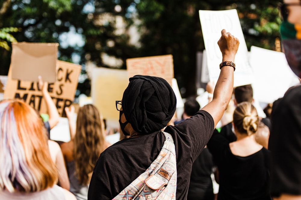 woman in black hijab holding white printer paper