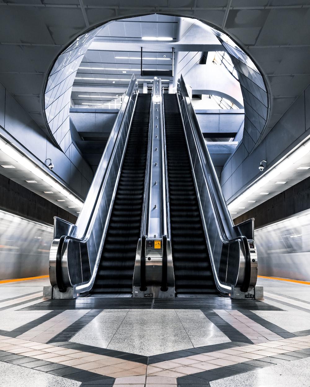 black escalator in a white tunnel
