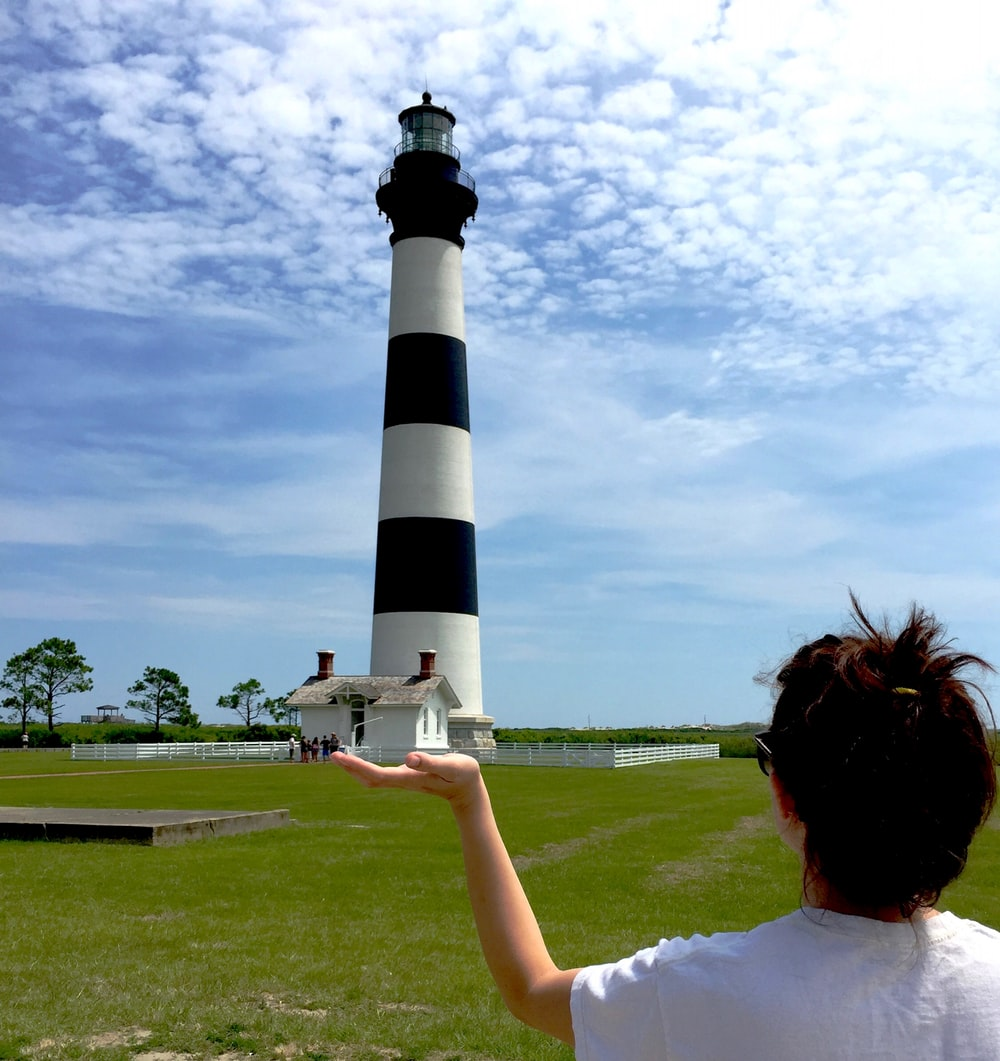 woman in white t-shirt holding black and white lighthouse under white clouds during daytime