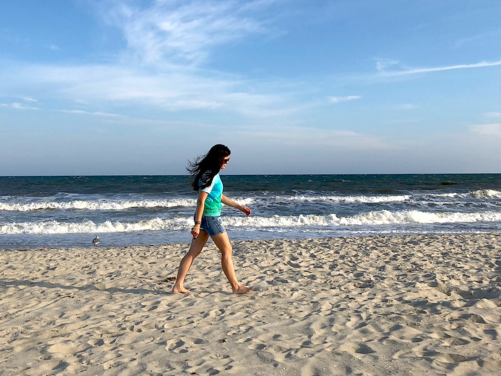 woman in blue tank top running on beach during daytime