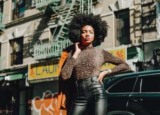 woman in black and white polka dot shirt and black denim jeans leaning on black car