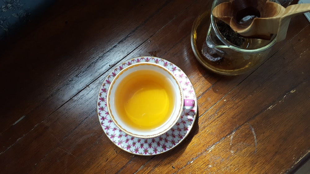 clear glass cup with yellow liquid on white and blue ceramic saucer