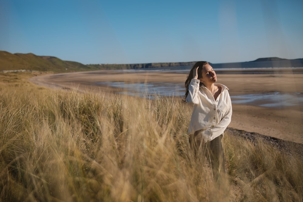 woman in white long sleeve shirt standing on green grass field near body of water during
