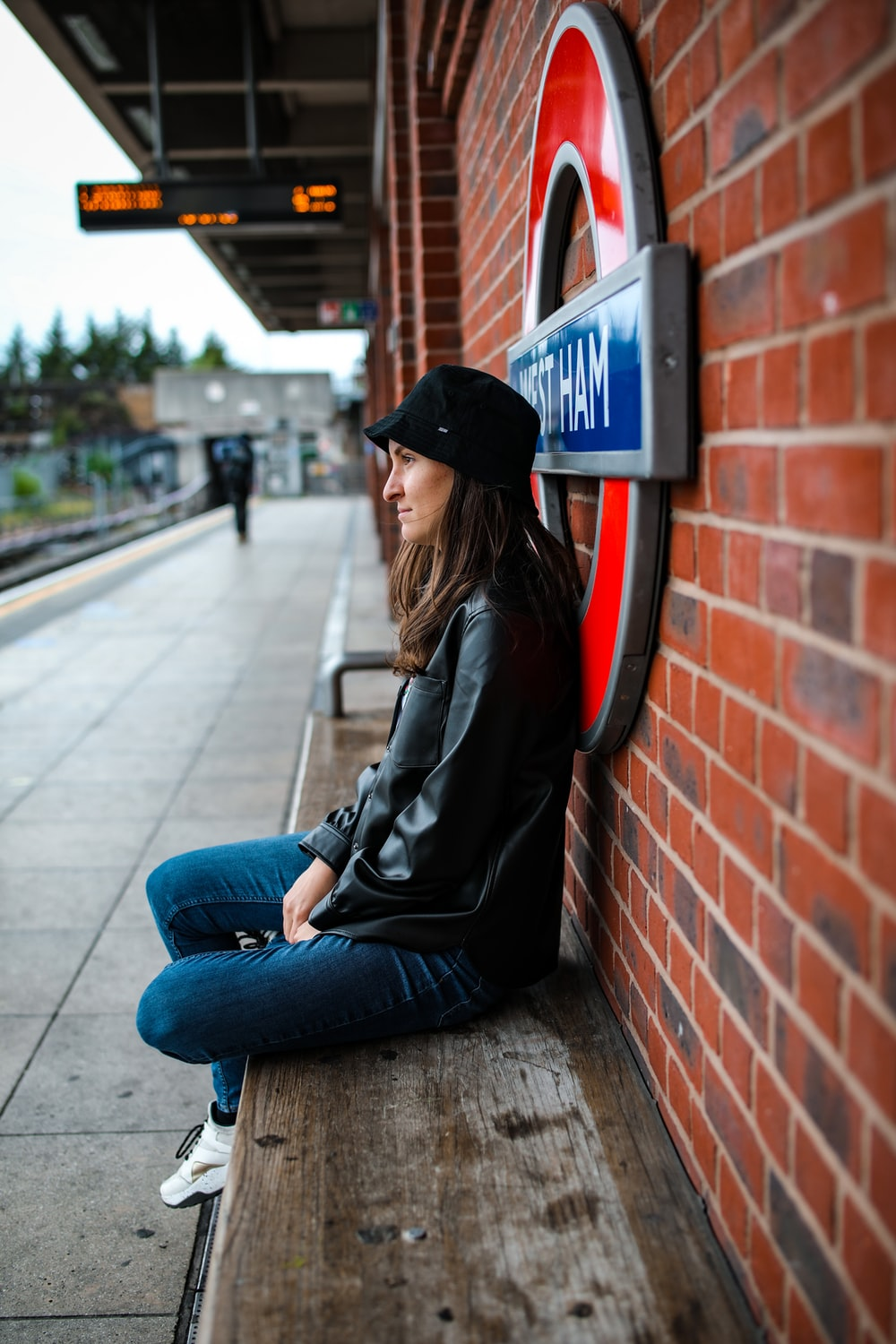 woman in black jacket and blue denim jeans sitting on red brick wall during daytime
