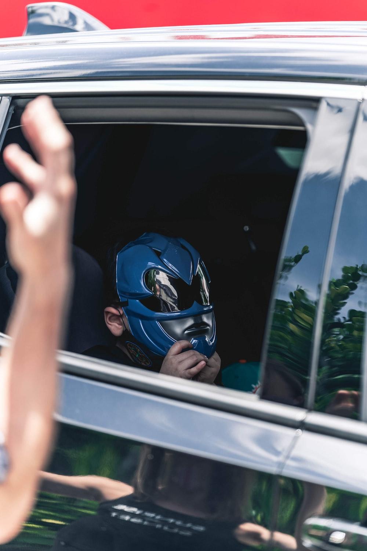 man in blue helmet in white car