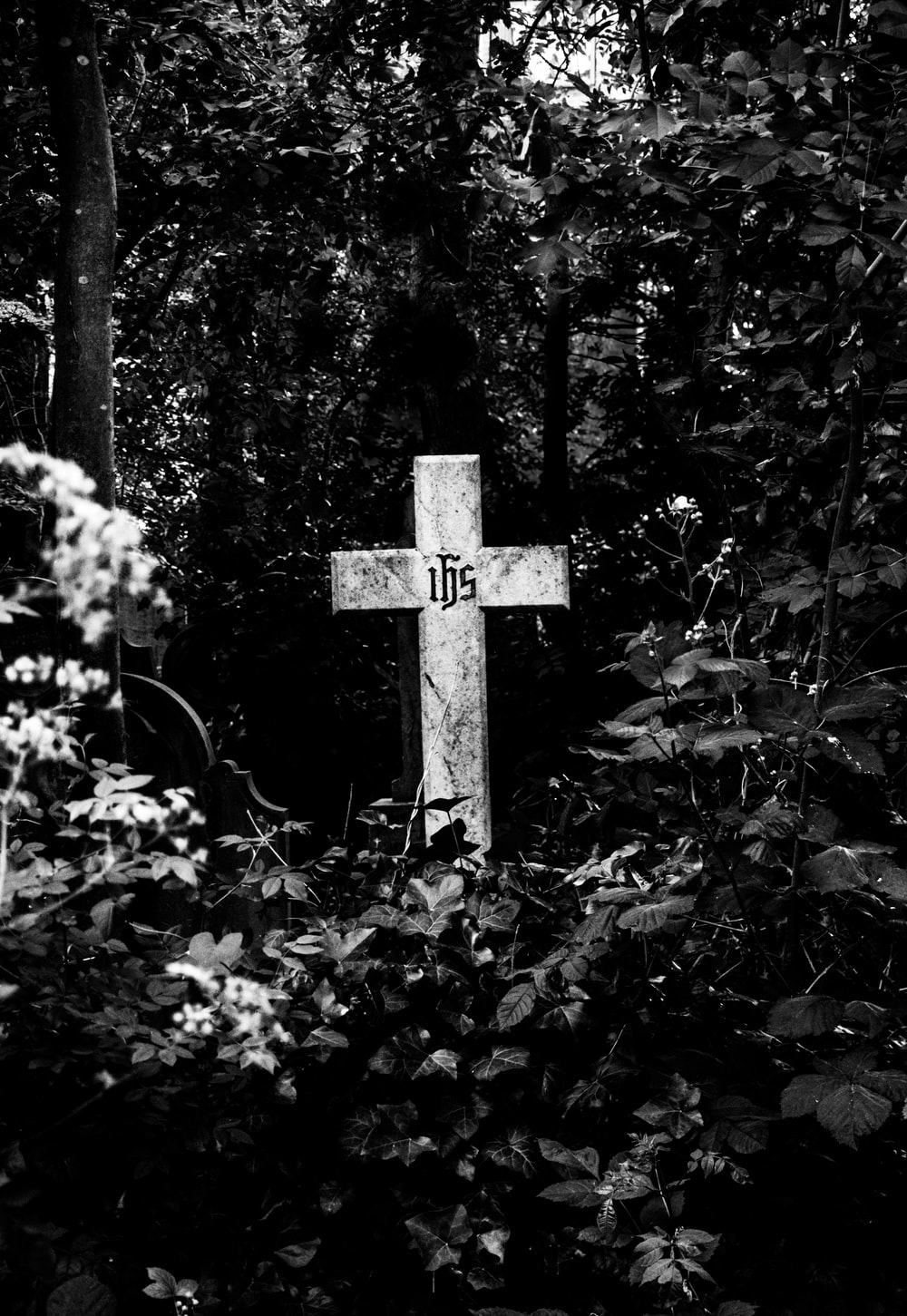 grayscale photo of cross surrounded by trees