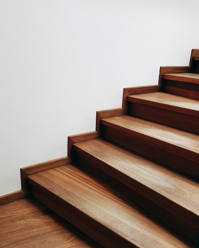 brown wooden staircase near white wall