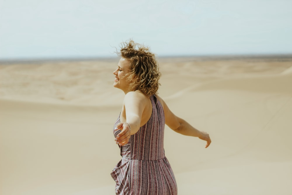 woman in white and purple stripe tank dress standing on brown sand during daytime