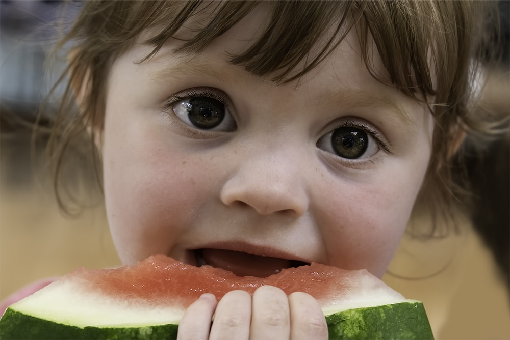 child eating watermelon during daytime