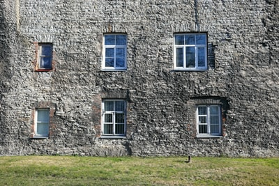 brown brick building with white wooden window estonia teams background