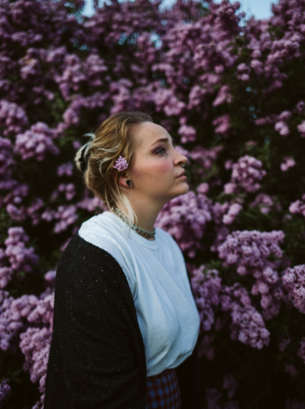 woman in black cardigan and white shirt standing near purple flowers