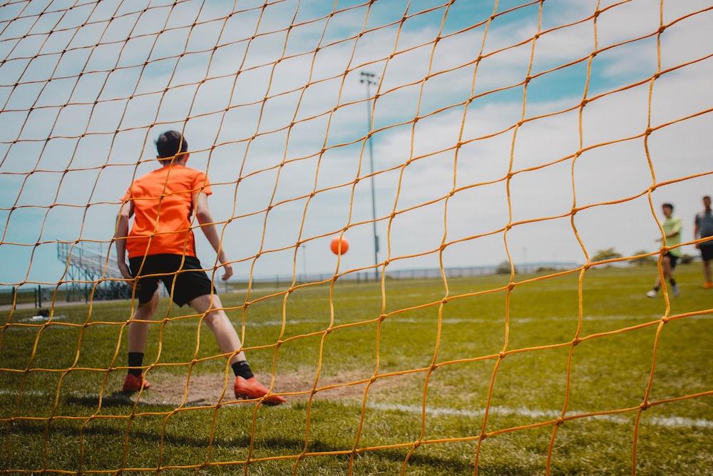 boy in orange shirt and black shorts playing soccer during daytime