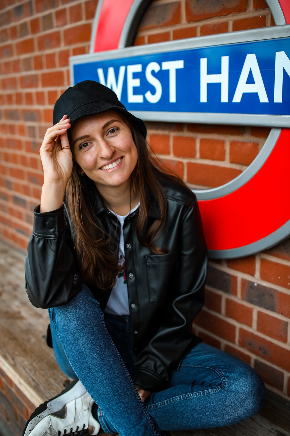 woman in black leather jacket and blue denim jeans sitting on brown concrete bench