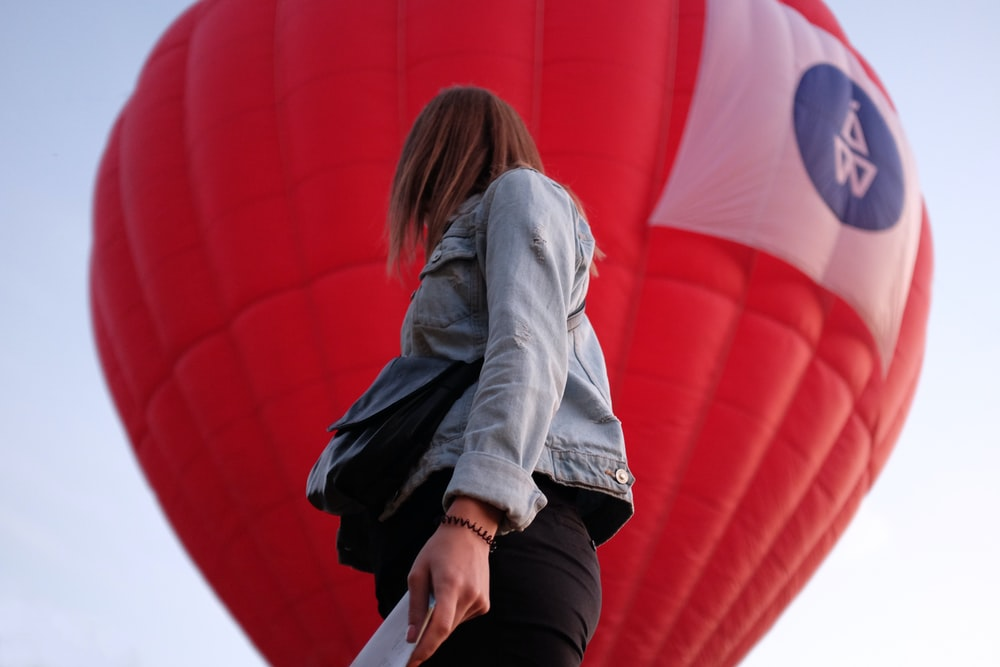 woman in gray hoodie and black pants sitting on red hot air balloon