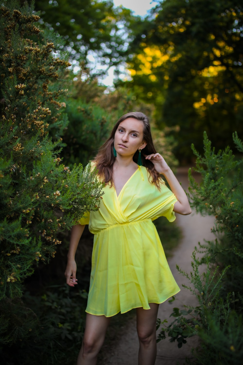 woman in yellow sleeveless dress standing beside green plant during daytime