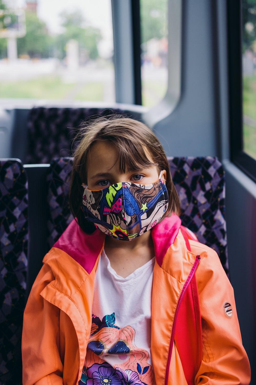 girl in orange jacket wearing blue mask