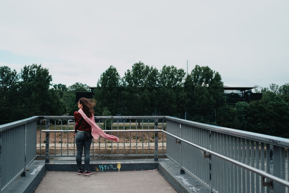 woman in red shirt and blue denim jeans walking on gray concrete bridge during daytime