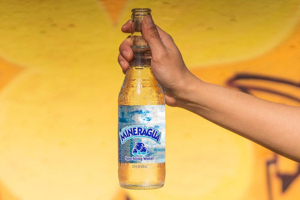 person holding blue moon belgian white bottle