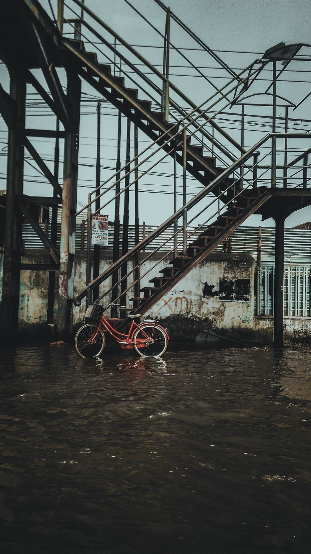 red bicycle on black metal ladder