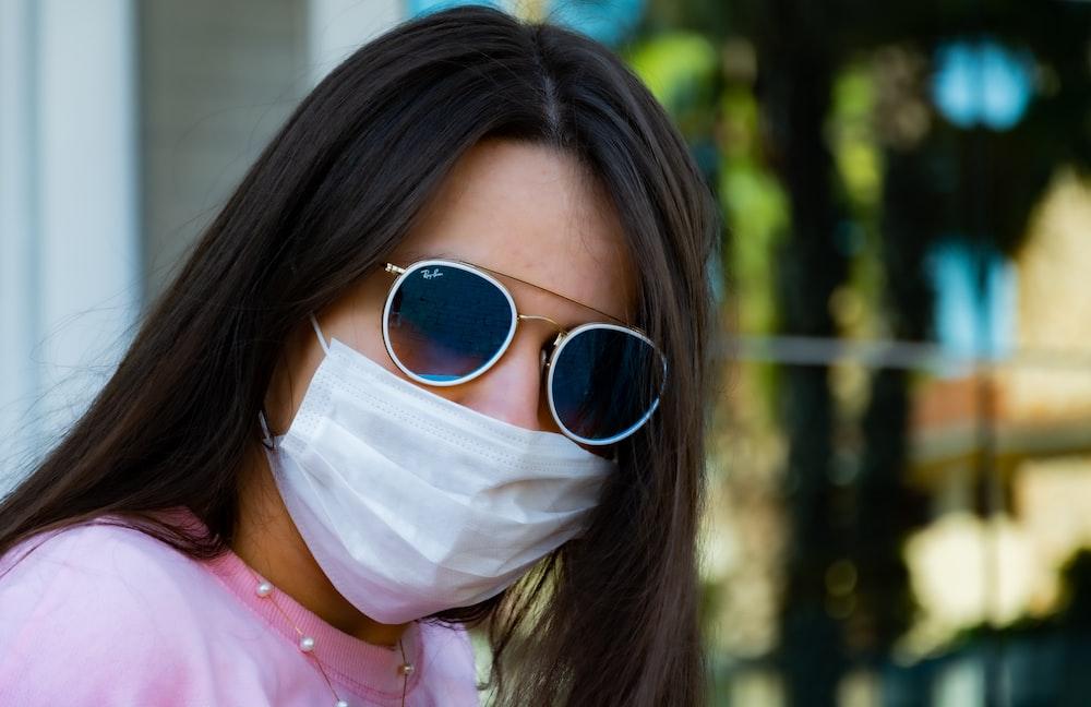 woman in pink shirt wearing white mask