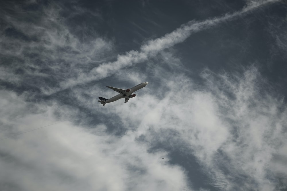 white airplane flying in the sky during daytime