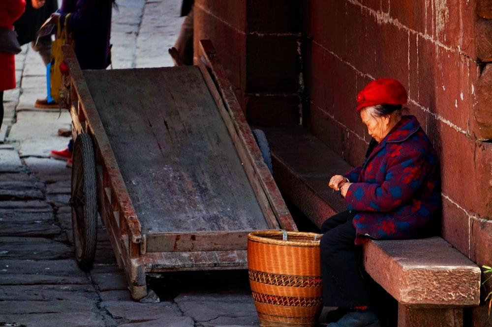 man in purple jacket sitting on brown wooden bench
