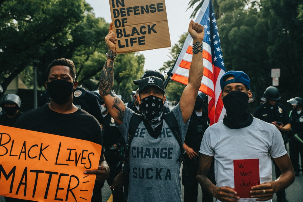 man in black crew neck t-shirt holding american flag