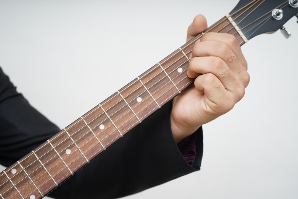 person playing brown acoustic guitar