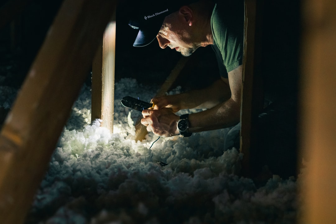 man working in dark attic of house with headlamp for light source