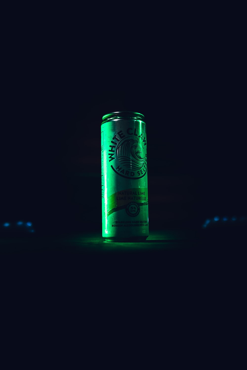 green and white can on black surface