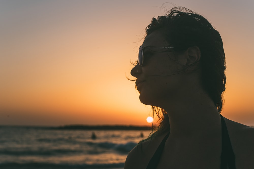 woman in brown jacket standing on beach during sunset