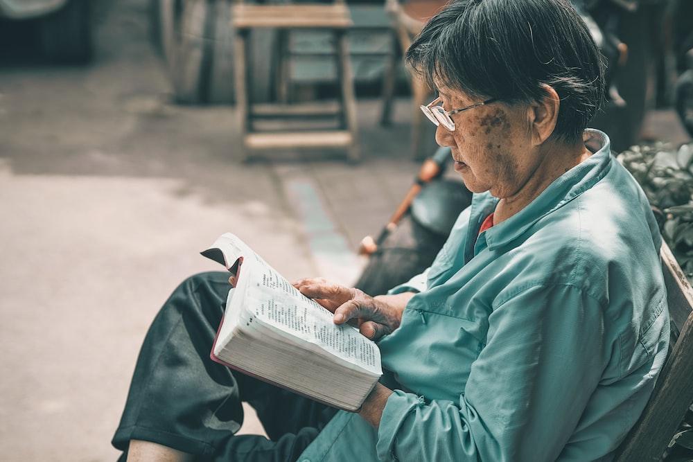 man in teal dress shirt reading book