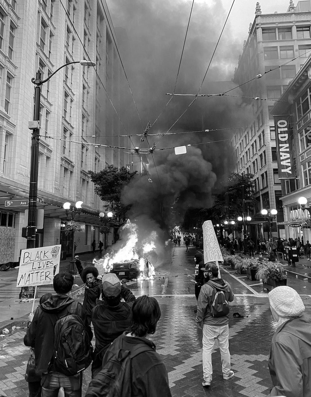 grayscale photo of people walking on street with smoke