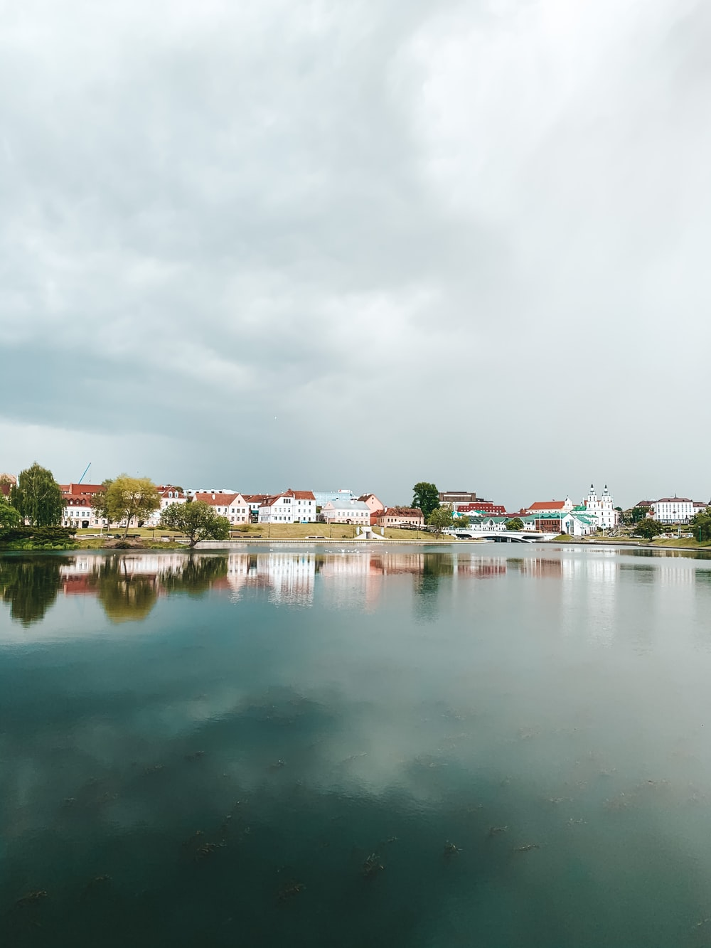 houses near body of water under cloudy sky during daytime