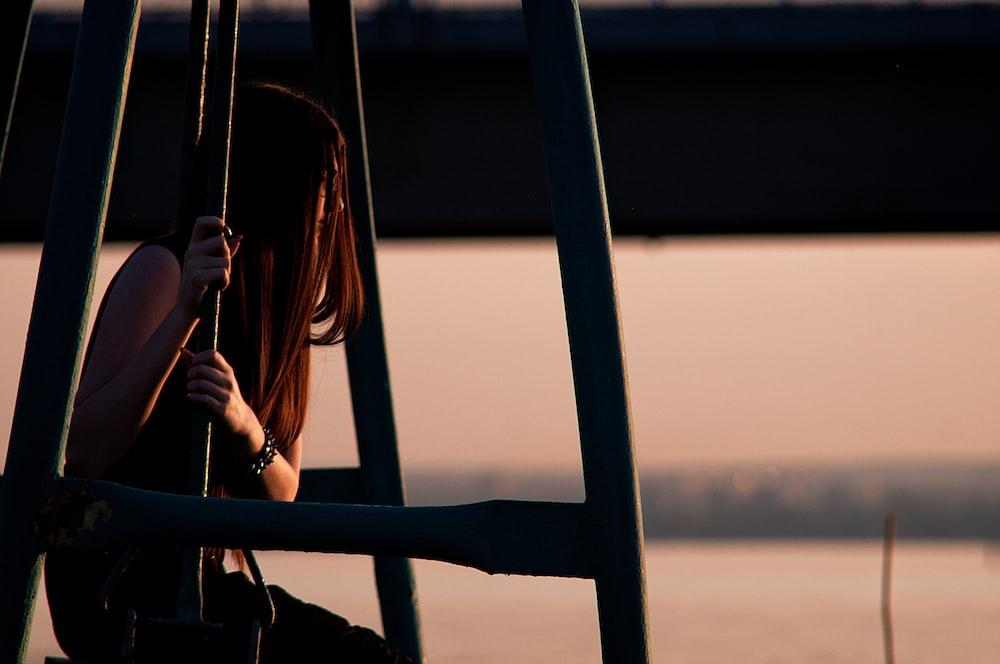 woman in black tank top standing beside black metal railings during sunset