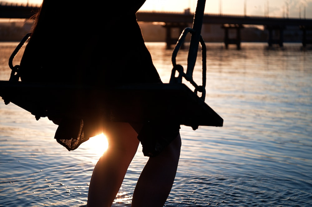 person sitting on swing near body of water during sunset